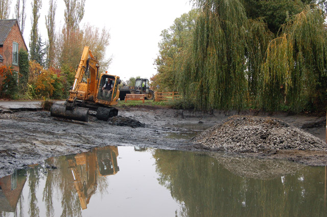 Dredging a pond with excavator